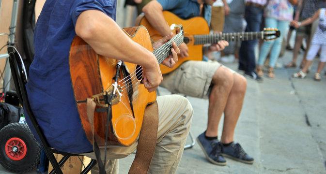 artisti di strada con chitarra, con pubblico sullo sfondo