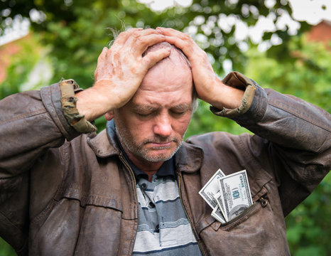 Stressed farmer with money in his jacket
