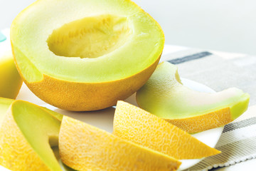Sliced yellow melon on white plate