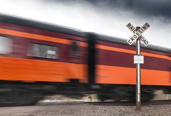 Orange & Maroon Passenger Car Flies by Railroad Crossing