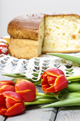 Red tulips in front of easter yeast cake. Selective focus