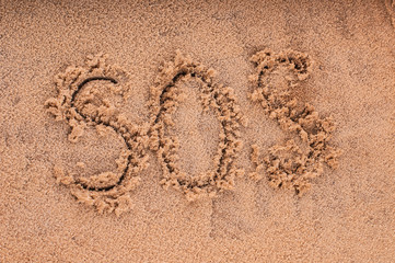"Drawing of ""SOS"" on the beach sand at the sea."