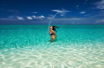 Woman splashing water with hair in the ocean