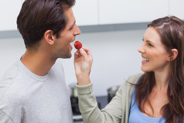 Woman feeding her husband cherry tomato