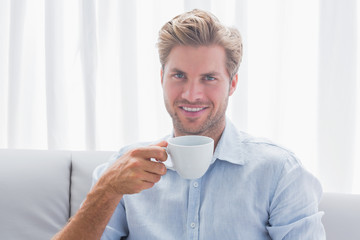 Handsome man sitting on his couch drinking a coffee