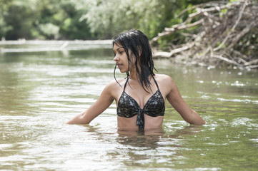 Beautiful woman swimming in river on hot summer day
