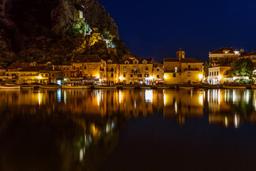 Fototapete - Illuminated Pirate Castle and Town of Omis Reflecting in the Cet