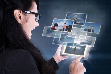 Excited businesswoman looking at success pictures on tablet