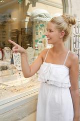 Lachende junge Frau beim Shoppen - Schmuck kaufen