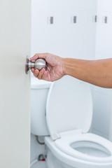 Man hand open toilet door