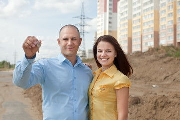 happy couple in front of new home