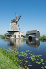 Dutch windmill at a canal on a sunny summer day