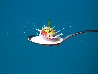 High-speed photo of strawberries falling into milk