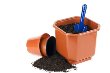 Flower pots with soil and shovel isolated on white