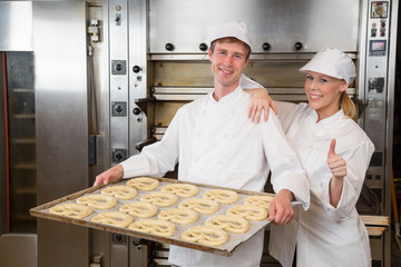 Two bakers with griddle full of pretzels