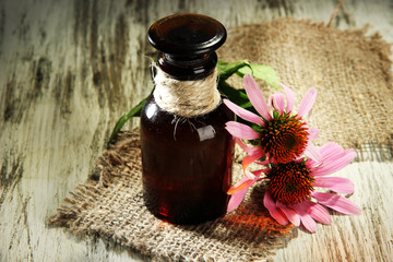 Medicine bottle with purple echinacea flowers on wooden table Wall mural