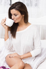 Beautiful woman on the bed with coffee