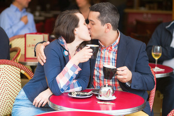 Couple in a Parisian street cafe, kissing