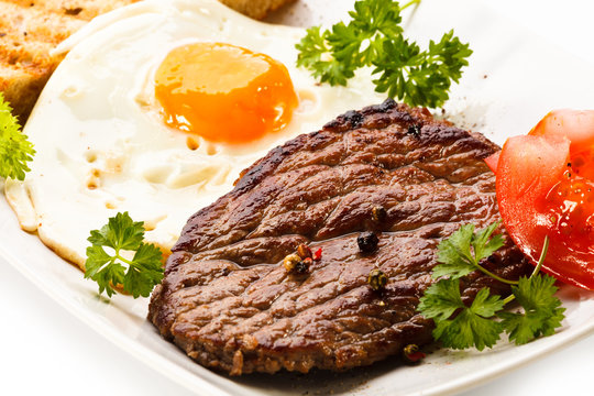 Grilled steak, toast, fried egg and vegetables