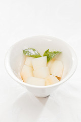 Fresh melon cubes with mint leaves