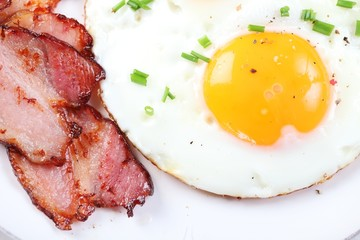 Close-up of fried egg and bacon on plate.