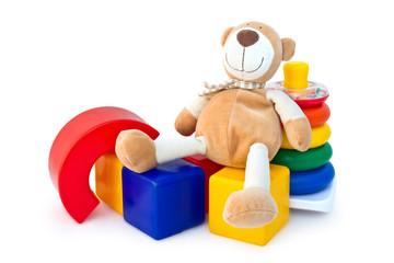 Box of bricks with a teddy bear and a pyramid.
