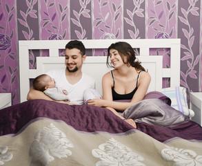 Happy parents in bedroom with baby