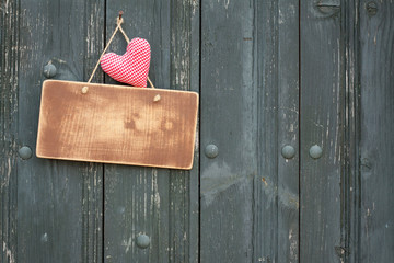 Wooden signboard with love heart on planks background