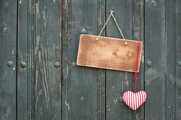 Wooden signboard with love heart hanging on planks background