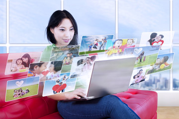 Asian female looking at online photos in apartment