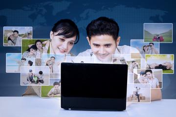 Happy couple search digital photos worldwide on blue