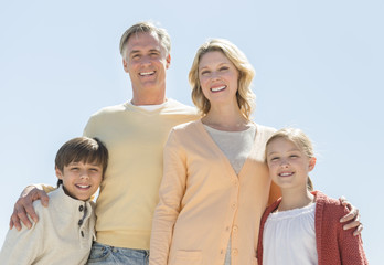Happy Family Of Four Standing Against Clear Blue Sky
