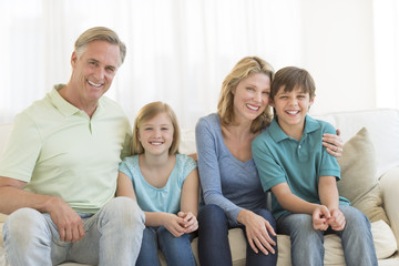 Family Of Four Smiling Together On Sofa