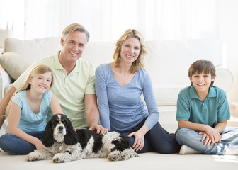 Family With Pet Dog Sitting On Floor In Living Room