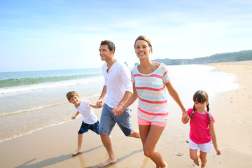Wall Mural - Happy family running on the beach