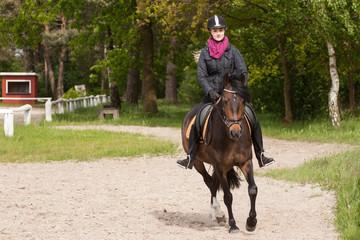 Mädchen reitet auf ihrem Pony