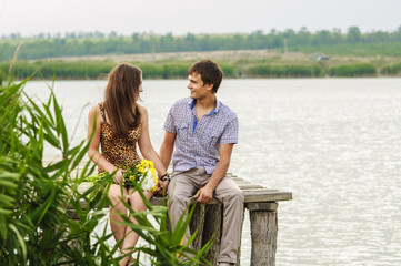 young girl and the young man on the dock by the river