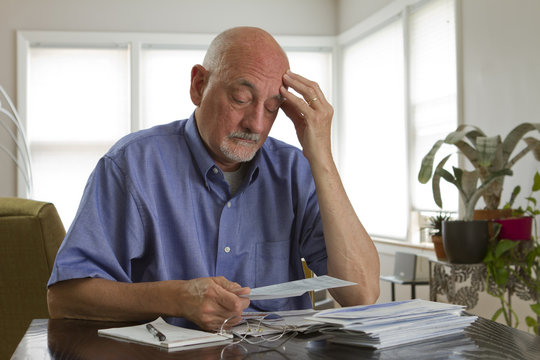 Older man paying bills, horizontal