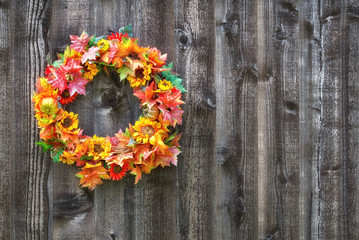 Autumn flower wreath hanging on rustic wooden fence