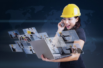 Excited contractor looking at laptop on blue