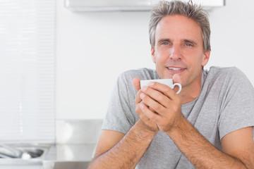 Happy man having coffee in kitchen