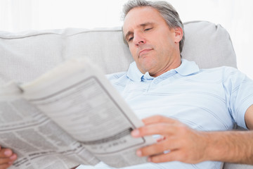 Man reading the news on couch