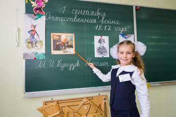 Little school girl stands at blackboard with a pointer