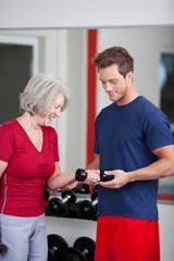 trainer mit seniorin im fitnessstudio