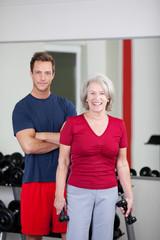 seniorin mit trainer im fitnessstudio