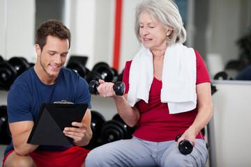 trainer berät seniorin im fitnessstudio