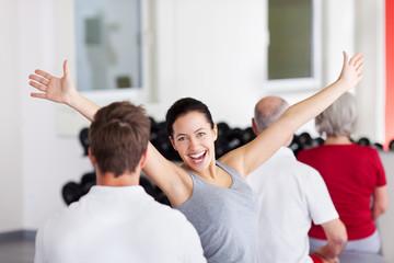 frau jubelt im fitnesskurs