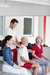trainer berät älteren mann im fitnessstudio