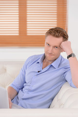 Tired businessman at home. Young red hair businessman sitting on