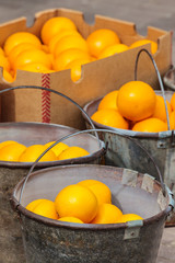 Fresh oranges in metal buckets on a market